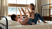 Happy mommy and kid daughter playing patty cake in bedroom