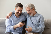 Happy family old father embracing young son enjoying using smartphone