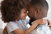 Cute little african daughter embrace touch noses with happy dad