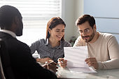 Clients couple read contract conditions in agent office