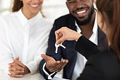 Female relator hand keys to happy diverse couple
