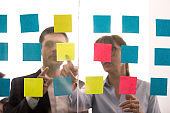 Diverse colleagues discuss ideas shared on sticky notes