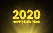 Merry Christmas and Happy New Year 2020. Golden numbers on black backdrop. Luxury text template. Gold backlight and magic dust. Shining numbers. Vector illustration