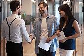 Smiling employees handshake greeting in office hallway