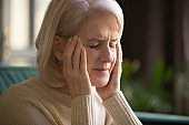 Close up grey haired woman suffering from headache, touching temples