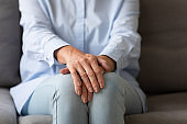 Senior lonely woman sit on couch with hands folded, closeup