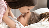 Loving mother kissing cute kid daughter waking up in morning