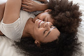 Affectionate african mom and child daughter embracing lying on bed