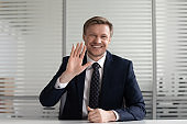 Smiling businessman waving having video call in office