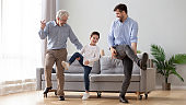 Happy three generation men family dancing together in living room