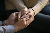 Close up aged couple holding hands, showing support and love