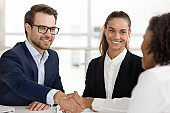 Happy hr handshaking hiring successful job candidate at business interview