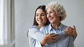Happy young granddaughter embrace smiling old grandma look through window