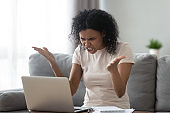 Angry stressed young black woman looking at laptop feeling annoyed