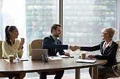 Happy middle-aged executive handshaking new male partner at team meeting
