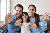 Smiling family with little kid waving talking on webcam