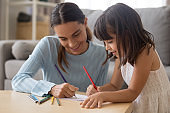 Happy young mom have fun drawing with little daughter