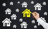 man drawing home icon on blackboard
