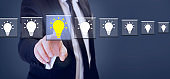 suit businessman touch yellow bright bulb on transparent screen