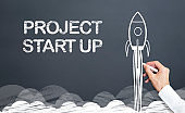 start up project concept with rocket on blackboard
