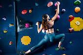 Muscle female woman climbing bouldering in training hall