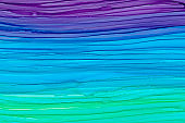 Horizontal colorful brush waves texture background. Hand drawn violet, blue and green liquid alcohol ink colors blending.
