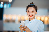 Happy young businesswoman using phone