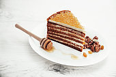 Honey cake with golden pearls and mint leaf and cinnamon on stone plate isolated on black background