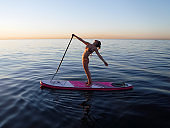 Hello Barcelona! Girl practicing yoga on SUP (Stand Up Paddleboarding) in the Mediterranean Sea