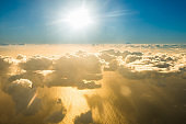 Airplane view of clouds, ocean and bright sun