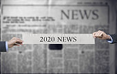 2020 NEWS - hand holding newspaper slogan.