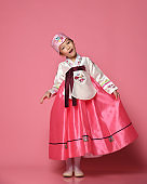 Korean little baby girl in traditional silk dress for new year celebration dancing on pink