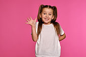 Little girl with ponytails, dressed in white t-shirt is posing against a pink studio background. Close-up shot. Sincere emotions