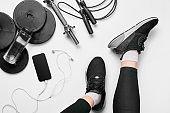 Women's legs in sneakers, fitness clothing, smartphone, dumbbells, headphones, top view.