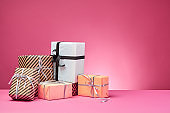 Different sizes, colorful, striped and plain paper gift boxes tied with ribbons and bows on a pink surface and background. Close-up, copy space
