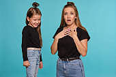 Mom and daughter with a funny hairstyles, dressed in black shirts and blue denim jeans are posing against a blue studio background. Close-up shot
