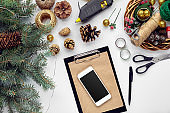 Preparing for Christmas or New Year holiday. Flat-lay of fur tree branches, wreaths, rope, scissors, craft paper over white table background, top view.