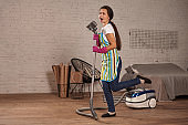 Happy woman cleaning home,dancing with vacuum cleaner and having fun, copy space.