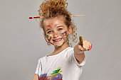 Beautiful little girl with a painted fingers is posing on a gray background.
