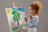 Charming school girl is painting with a watercolor brush on an easel, standing on a gray background.