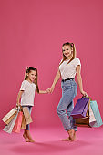 Mom and daughter with ponytails, dressed in white t-shirts and blue jeans are posing against pink background with packages in hands. Full length