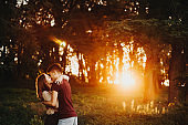 Amazing couple embracing and hugging against sunset light in the park while walking after work.