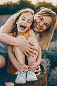 Portrait of a lovely little girl laughing with closed eyes while is embraced by her mother with is laughing and looking at camera against sunset.