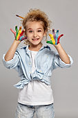 Beautiful little girl with a painted hands is posing on a gray background.