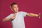 Close-up portrait of a blonde teenage boy in a white t-shirt posing against a pink studio background. Concept of sincere emotions