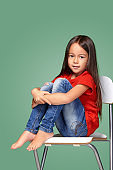 little girl wearing red t-short and posing on chair