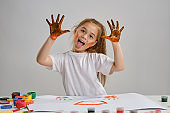 Little girl in white t-shirt sitting at table with whatman and colorful paints, showing her painted hands. Isolated on white. Medium close-up