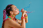 Lovely girl with a multi-colored braids hairstyle and bright make-up, is blowing bubbles using tubules, posing in studio against a blue background