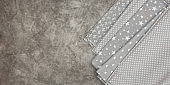 Natural grey fabrics and textiles on grey background. Sewing industry concept. With copy space