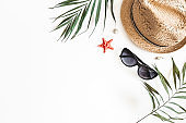 Summer composition. Tropical palm leaves, hat on white background. Summer concept. Flat lay, top view, copy space